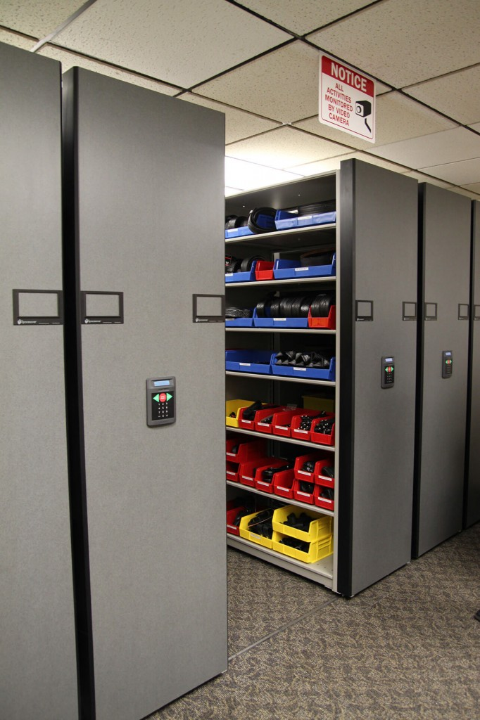 Duty Belts and holster storage in bins on mobile shelving at Aurora Police Dept.